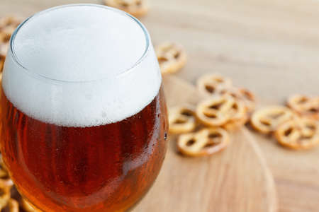 A glass of cold foamy beer with pretzels. Bavarian Oktoberfest snacks and drink on wooden background