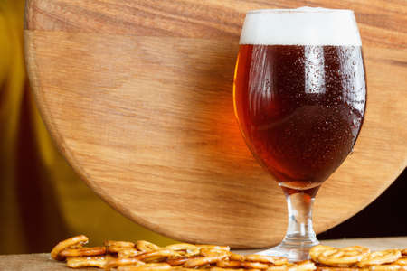 german alcohol: Glass of foamy beer alcohol with german pretzel. Traditional bavarian Oktoberfest snacks and drink in bar on wooden background Stock Photo