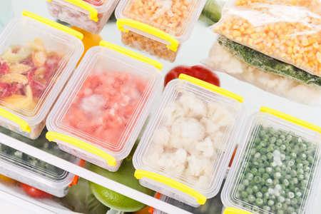 Fagyasztott ételt a hűtőszekrénybe. Zöldség a fagyasztó polcain. Húslisztkészlet a tél. Stock fotó