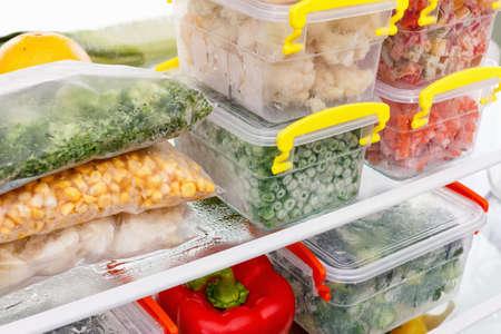 Gefrorene Lebensmittel in den Kühlschrank stellen. Gemüse auf den Gefrierrosten. Die Bestände an Essen für den Winter. Standard-Bild