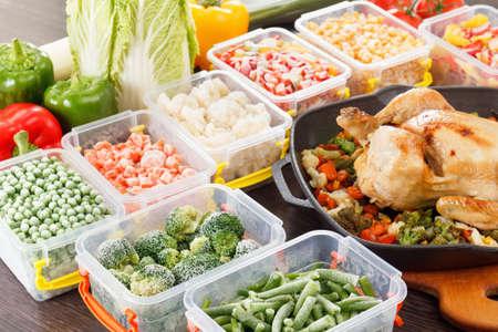 alimentos congelados: Revuelva freír verduras congeladas en un recipiente de plástico, pollo y verduras asadas. congelador de alimentos saludables en la bandeja. Foto de archivo