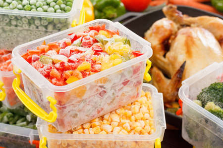 listeria: Frozen foods vegetables cook in plastic containers, fried chicken in pan. Healthy freezer meals. Stock Photo