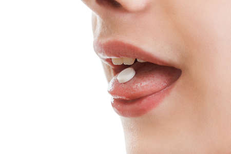 human body substance: Young man taking drug in him mouth. The drug addict putting a pill, isolated on white
