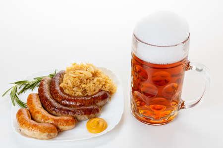 Octoberfest menu, beer mug with foam, a plate of sausages and sauerkraut. Oktoberfest meal.