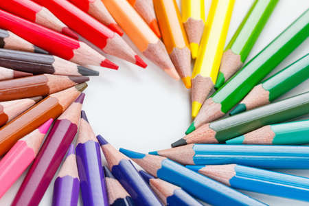 Colorful bunch of multicolored vibrant colored pencils on white background closeup
