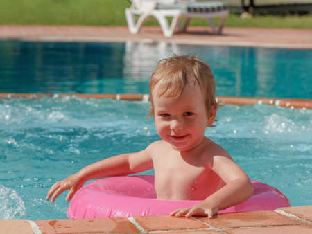 Little boy playing in the pool on a summers day holiday Stock Photo