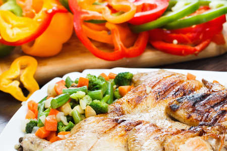 Chicken roasted on grill in the background bell pepper with vegetables Stock Photo