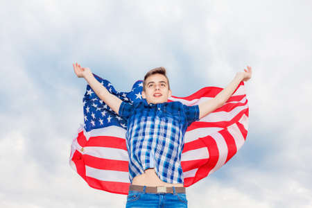 USA flag is held by a running guy in the background of a summer sky Outdoor Stock Photo