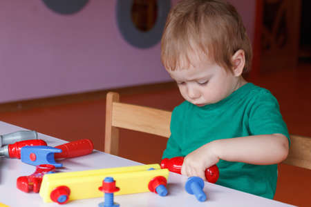 Little boy, the child plays with blocks and toys at the table