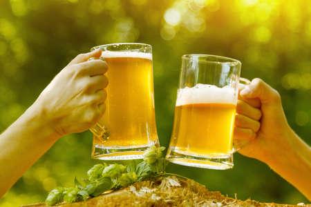 Man hand clink beer woman nature fun octoberfest. Standard-Bild