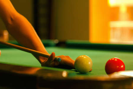 Playing man by cue in billiard pool activity background close-up.