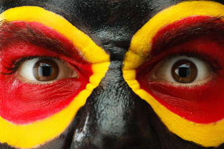 Germany sports fan patriot. Painted colors country flag on angry man face. Devil savage Eyes close up Stock Photo