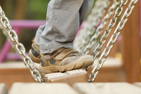 Child playing at the attractions of the swings in the park, legs close-up