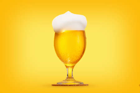 brewery: Glass pint of beer close-up with froth over yellow background