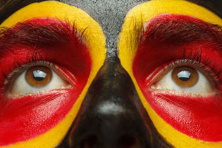 German or Belgian sports fan patriot. Painted country flag on man face. Eyes close up