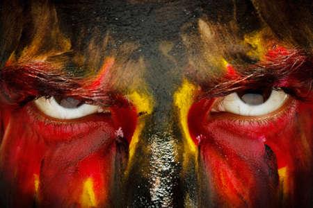 Patriote amateur de sport allemand ou belge. Drapeau de pays de couleurs peintes sur le visage de l'homme en colère. Les yeux du diable sauvage se bouchent