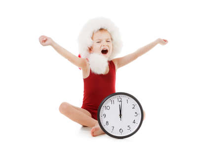 Emotional portrait caucasian little boy wearing Santa Claus red hat. Funny cute smiling child with big clock isolated on white. Winter holiday christmas concept. Banque d'images