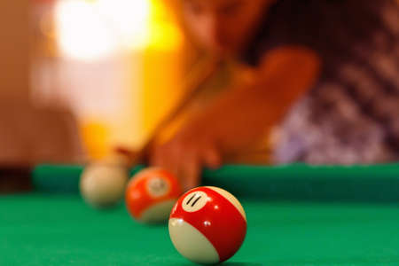 Playing man by cue in billiard balls pool activity.