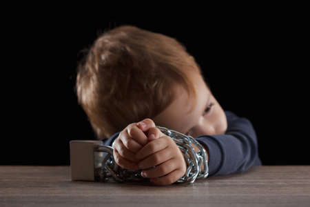 Child with chain tied, imprison, retarded, Child Abuse on black abstract