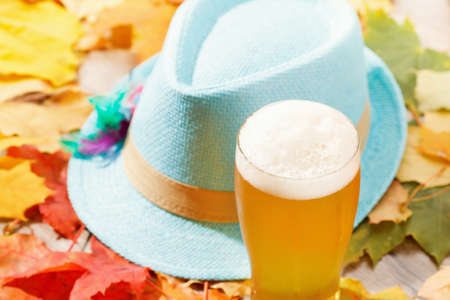 Beer glass pint octoberfest picnic on background with hat and autumn yellow leaves