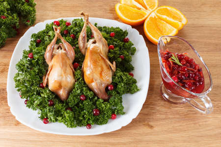 Carcasses of quail roasted with sweet and sour cranberry sauce and parsley on a wooden table