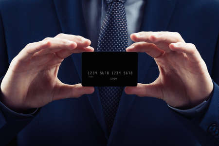 Businessman in costume and necktie hold credit card, close up. Black background isolated concept of e-business shopping, money pay payment buy