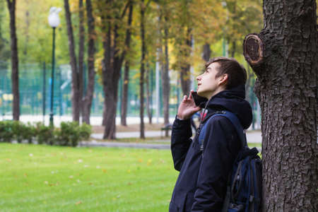 Portrait of Tenager guy with a smartphone talking phone in the Park outdoor.