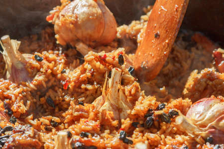 Preparation of pilaf on fire. Tourist bowler with food on bonfire, cooking in the hike, outdoor activities.
