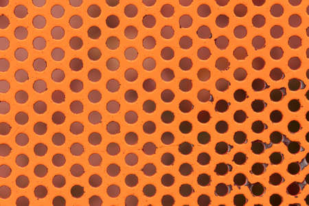 Orange painted circle perforated metal panel for texture and background
