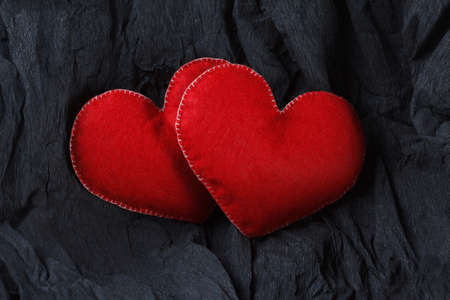Love concept, red hearts on black paper texture. Dark background with two felt hearts for use in graphic design. Valentines style, St. Valentines Day.
