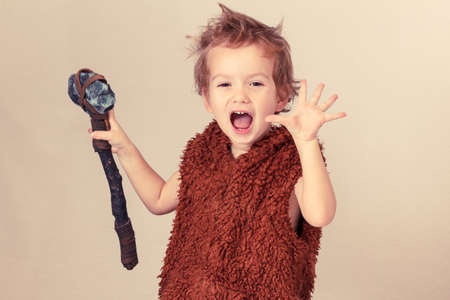 Cute cheerful naughty child playing with axe. Humorous concept ancient caveman on white background