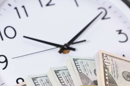 Time is money clock concept. Dollar bills on the dial of the clock with arrows