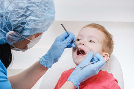 Dentist medical examination of child patient teeth using a mirror of instrument Caries, tooth close up damage, illness.
