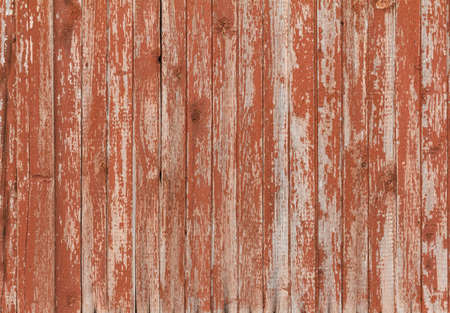 Background of old wooden board with peeling cracked red paint Stock Photo