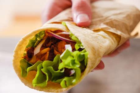 Mexicaanse burrito met kip, groenten, peper en bonen. Burrithos takos eten in de hand. Straat snel voedsel op witte achtergrond Stockfoto