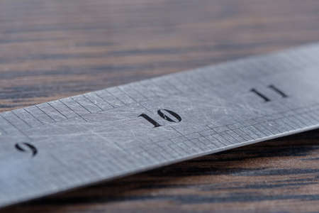 Metal ruler macro on a wooden background table