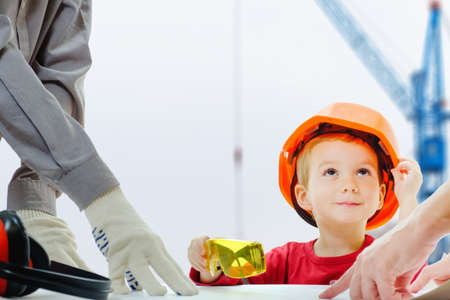 Concept, builders are discussing with child over the drawing. Helmet protective equipment construction city site with cranes Foto de archivo - 97539406