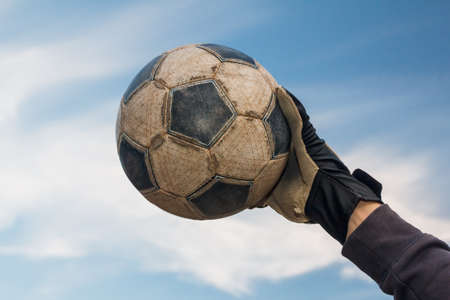 Football goalkeeper catching soccer old ball on blue sky with clouds Foto de archivo