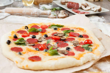 Assorted pizza with different fillings salamy, mushrooms served on wooden table with ingredients mushrooms, salami, peperoni, tomatoes, cheese
