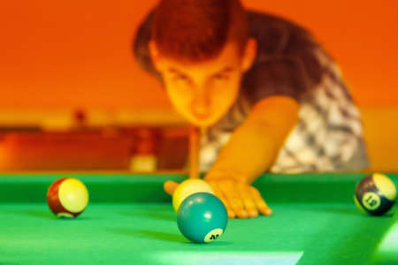 Playing man by cue in billiard pool activity sport game.