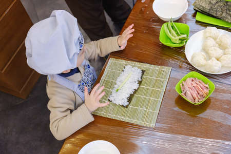 Cooking, Preparation of traditional sushi rolls. The boy is dressed as a cook. Stock Photo