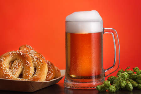 Pint of beer with ingredients for homemade beer on red background with pretzel