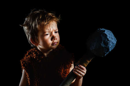 Little funny boy is a Neanderthal or a Cro-Magnon. An ancient caveman with a huge ax is isolated on a black background. Shaggy and dirty savage, warrior Stock Photo