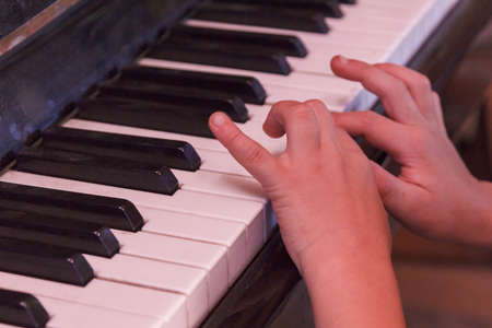 Child plays old piano his hands with fingers. Stock fotó