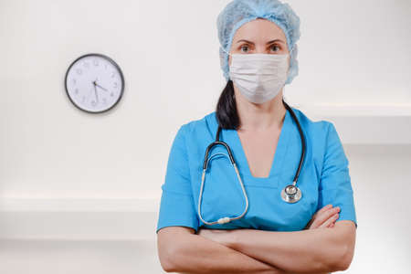 Medical doctor with stethoscope on white background. Female nurse wearing surgical mask and hat. Caucasian Woman Portrait. 写真素材