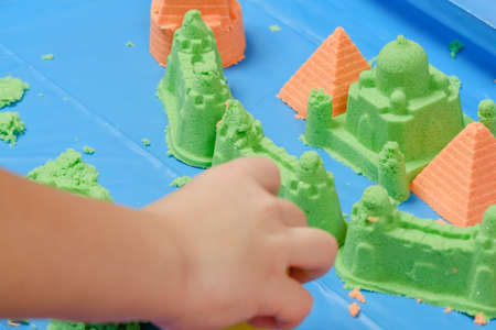 Children playing kinetic colored sand. Kids Games