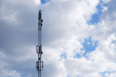 Mobile phone cellular tower silhouette with evening blue sky with clouds.