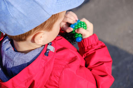 cute caucasian preschooler child playing hand made toy called slime.
