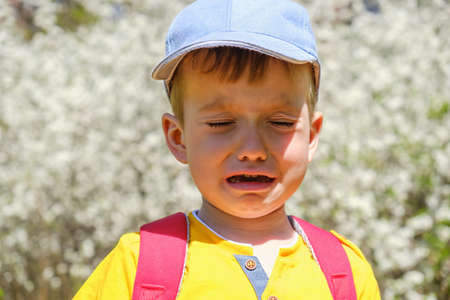 Caucasian boy portrait crying while standing up in park against flowering flower Stock Photo