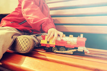 Child boy playing with toy train outdoors at warm summer day. Toys for little children